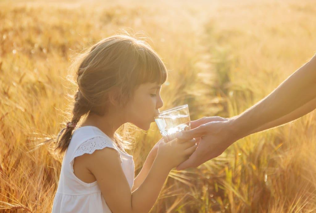 Petite fille qui boit un verre d'eau